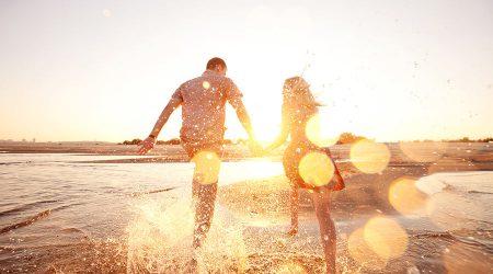 Glückliches Paar läuft durch flaches Wasser am Strand.