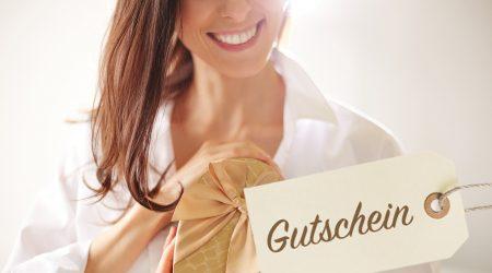 """Lächelnde Frau hält ein goldenes Paket mit Schleife und der Aufschrift """"Gutschein"""""""