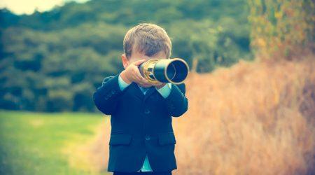 Kind schaut durch ein Fernrohr.