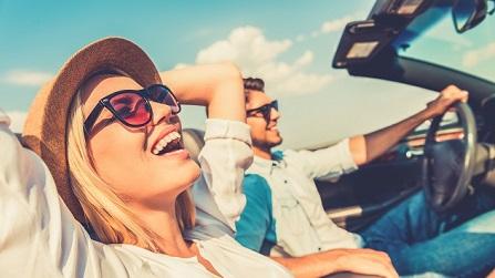 Lachende Frau mit Hut und Sonnenbrille neben einem Mann im offenen Cabrio unterwegs.