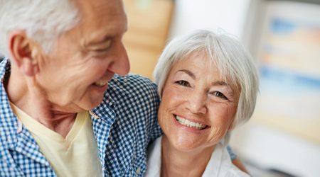 Ein älteres Paar umarmt sich und lächelt.