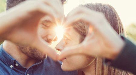 Mann und Frau blicken durch ein Herz.