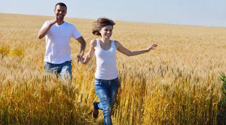 Glückliches Paar läuft durch Kornfeld