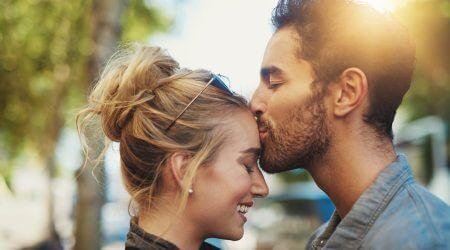 Mann küsst lächelnde Frau auf die Stirn.