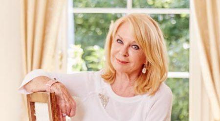 Gerda Rogers sitzt auf einem Sessel und lächelt.